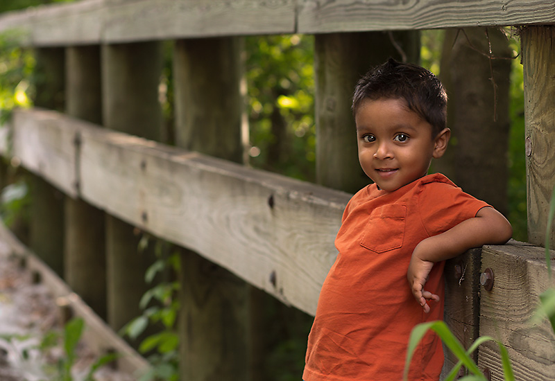 Children's photographer in Appleton, Wisconsin, toddler boy leaning on fence